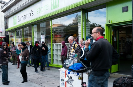 protester in front of bernardos charity shop to protest their involvement with immigration dention centres for children, by Anna Forgione