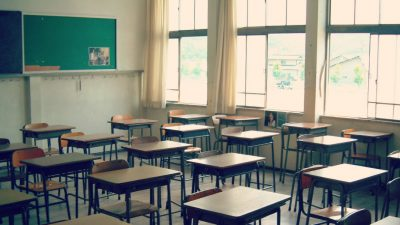 photo of empty school desks and large window in classroom