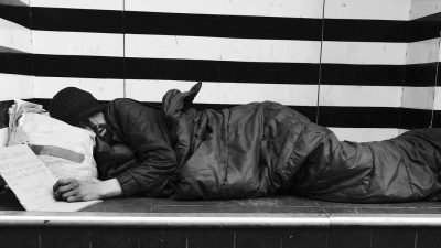 A homeless man asleep on a ledge. Photo by Allan Warren