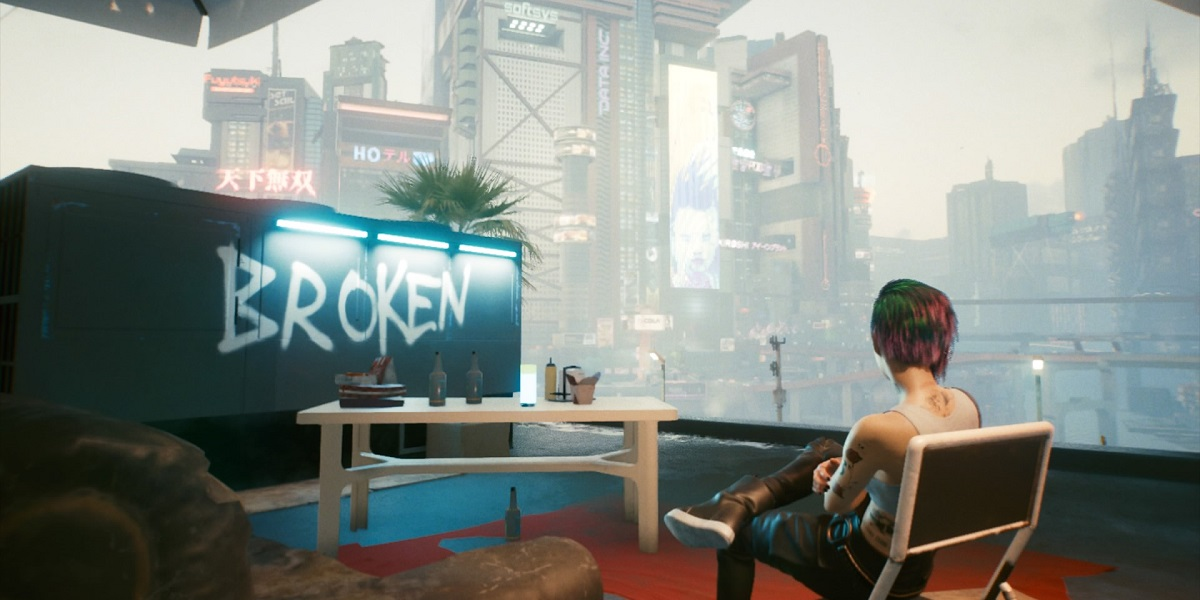 Screenshot from Cyberpunk 2077 showing a character from the game sitting in front of a futuristic cityscape and the word 'broken' graffitied onto a wall
