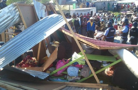 Shacks destroyed as people look on